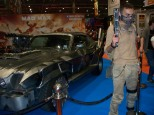 A car on display from Mad Max: Fury Road, with a cosplayer.
