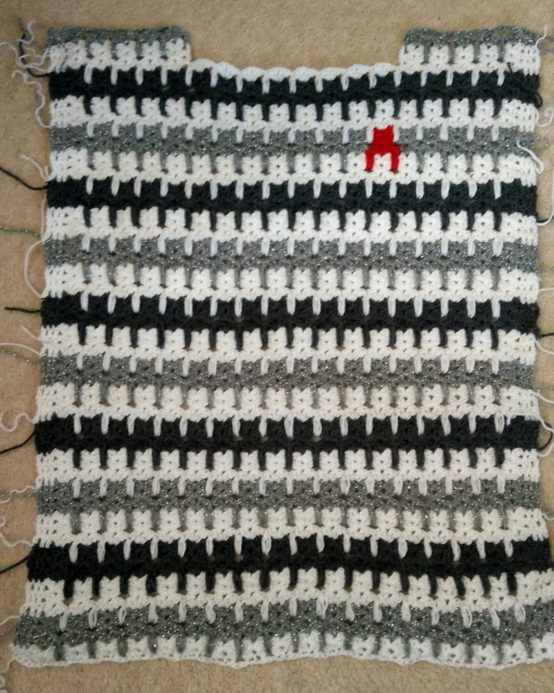 The completed front of the cat motif crochet jumper, with 3 colour stripe in white, dark grey, and light grey sparkle, with a red cat motif over the heart. All the ends of the yarn are visible and messy!